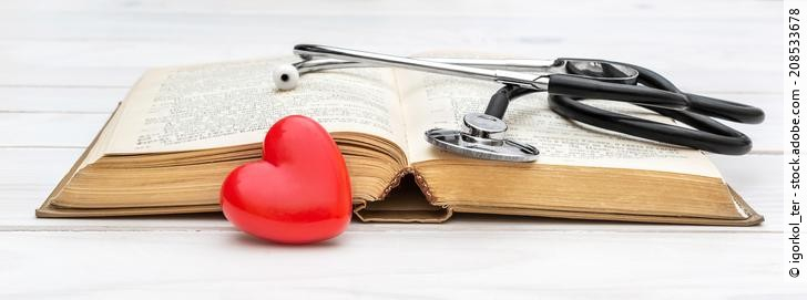 Opened book with stethoscope and red heart on white wooden table.